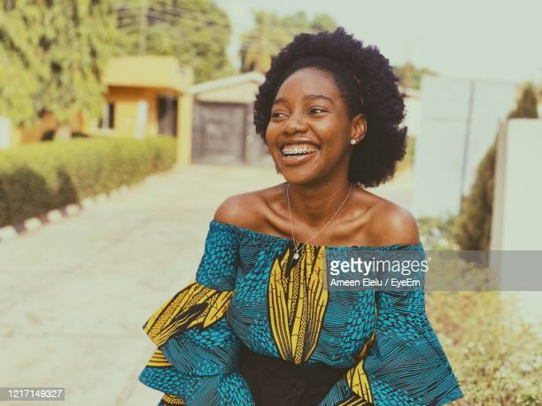 smiling young woman looking away against trees and sky - nigeria stock pictures, royalty-free photos & images