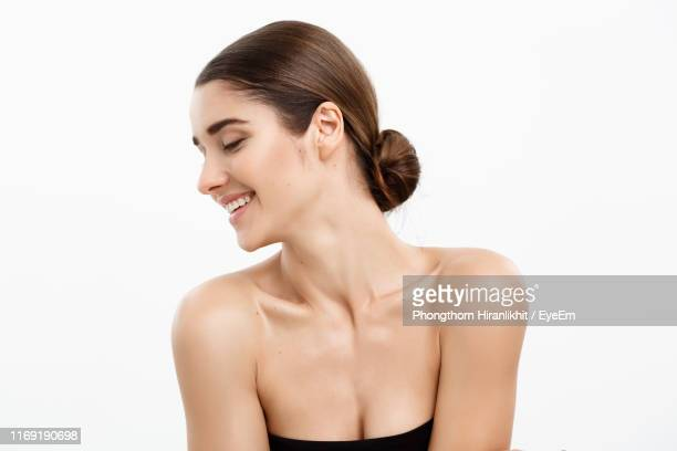 smiling young woman looking away against white background - cleavage stock pictures, royalty-free photos & images