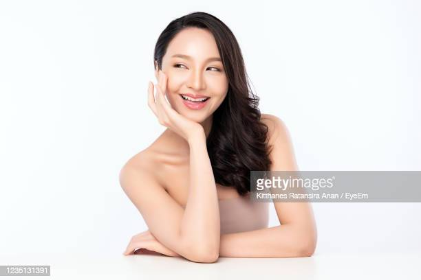 smiling young woman looking away against white background - 顎に手をやる ストックフォトと画像