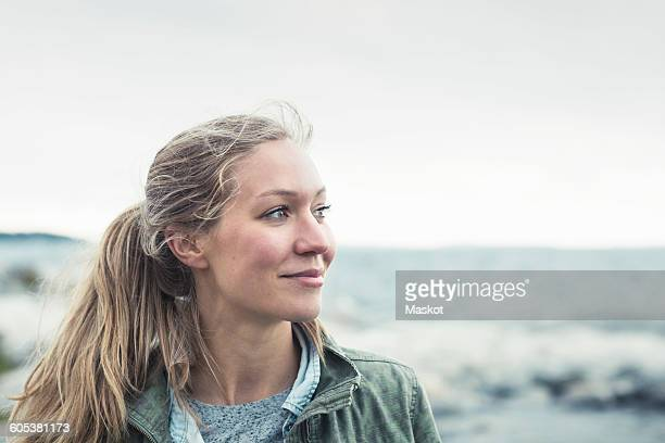 smiling young woman looking away by sea against sky - in den zwanzigern stock-fotos und bilder