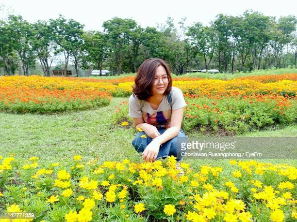 Smiling Young Woman Looking Away Crouching By Flowering Plants At Garden