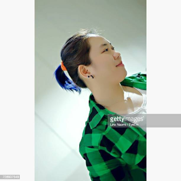 smiling young woman looking away standing against wall - west kalimantan stock pictures, royalty-free photos & images
