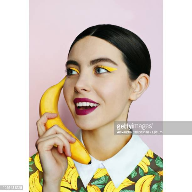 smiling young woman looking away while holding banana against pink background - red lipstick stock pictures, royalty-free photos & images