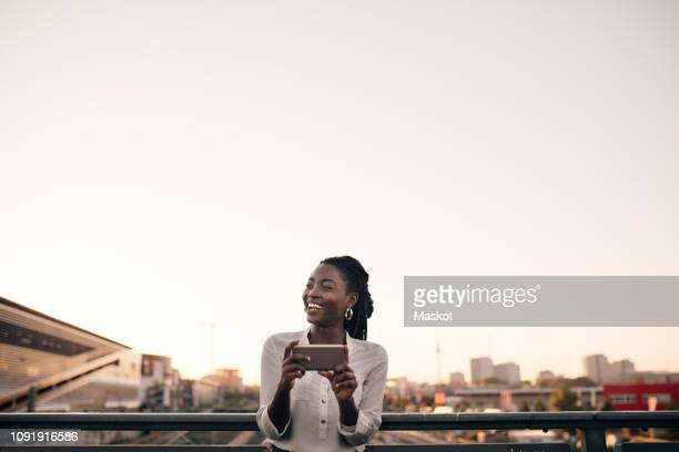 smiling young woman looking away while holding mobile phone against clear sky in city - milleniumgeneratie stockfoto's en -beelden