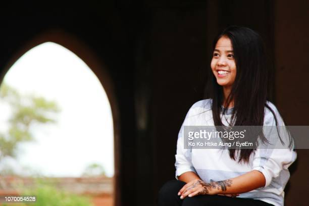 smiling young woman looking away while sitting against building - ko ko htike aung stock pictures, royalty-free photos & images