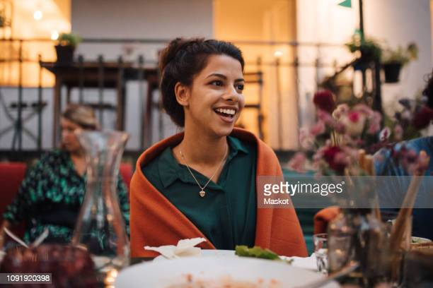 smiling young woman looking away while sitting at table during dinner party - invité photos et images de collection
