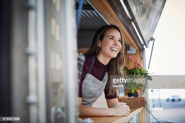 smiling young woman looking away while standing in food truck at city - food truck fotografías e imágenes de stock