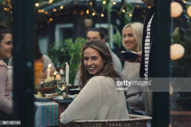 smiling young woman looking back while sitting with friends in glass conservatory in back yard - omkijken stockfoto's en -beelden