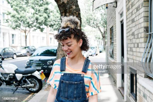 smiling young woman looking down on footpath by building - individuality stock pictures, royalty-free photos & images