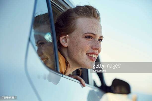 Smiling young woman looking out of a car