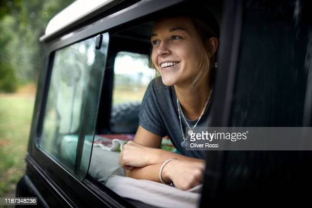 smiling young woman looking out of car window - vida simples imagens e fotografias de stock