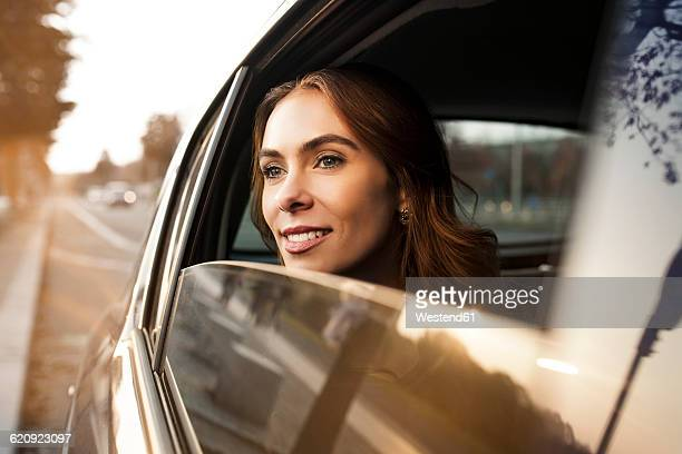 Smiling young woman looking out of car window