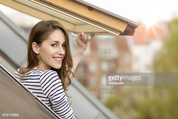 Smiling young woman looking out of roof window