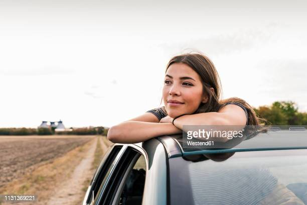 smiling young woman looking out of sunroof of a car - tagträumen stock-fotos und bilder