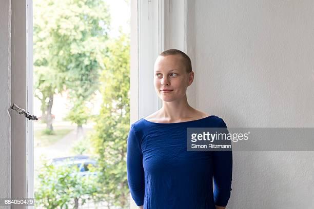 smiling young woman looking out of window - glattrasiert frau stock-fotos und bilder