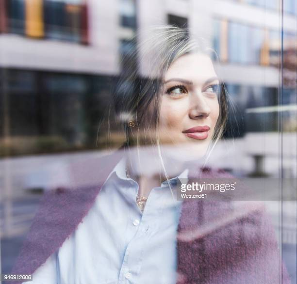smiling young woman looking out of window - reflet photos et images de collection