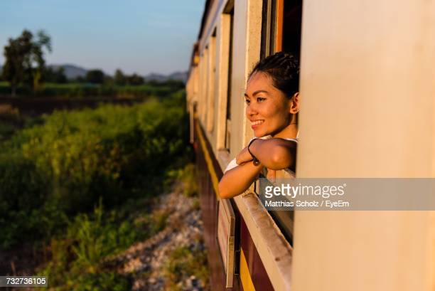 smiling young woman looking through train window - passenger train stock pictures, royalty-free photos & images