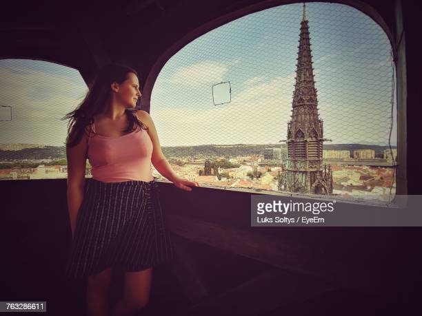 smiling young woman looking through window at observation point - kosice stock photos and pictures
