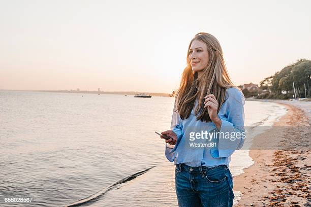 Smiling young woman lwith smartphone standing on the beach