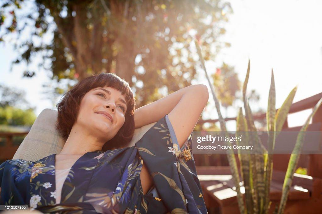 Mulher sorridente deitada em uma cadeira de convés pátio : Foto de stock