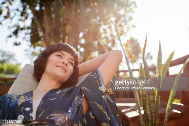 smiling young woman lying back in a patio deck chair - relaxation stock pictures, royalty-free photos & images