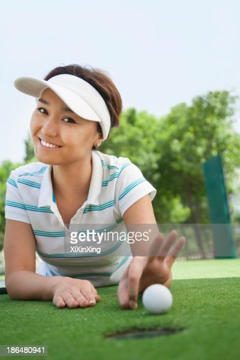 Smiling Young Woman Lying Down In A Golf Course Getting