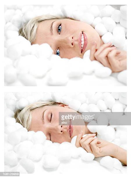 Smiling Young Woman Lying Down Surrounded by Cotton Balls