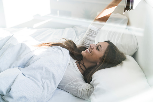 Smiling young woman lying in bed - gettyimageskorea
