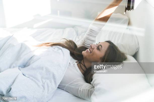smiling young woman lying in bed - waking up stock pictures, royalty-free photos & images