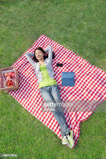 Smiling young woman lying on her back with arms behind her head on a blanket and relaxing in the park