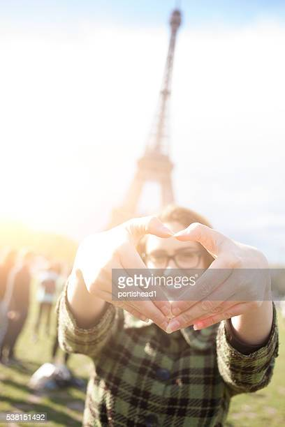 Smiling young woman making heart shape with fingers