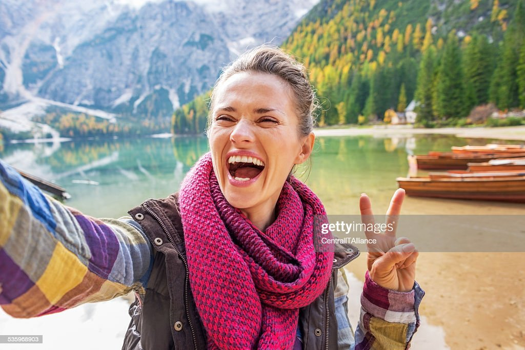 Smiling young woman making selfie on lake braies, italy : Stock Photo