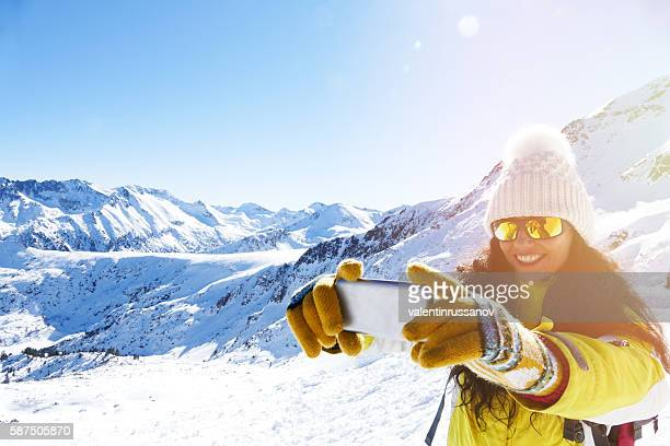 Smiling young woman making selfie on top of snow mountain