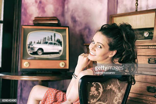 Smiling young woman making selfie with vintage camera