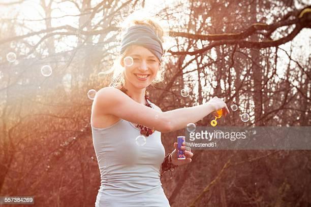 smiling young woman making soap bubbles - femme coquine photos et images de collection