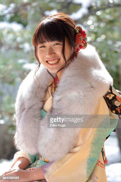 smiling young woman of coming‐of‐age ceremony sitting on chair - ストール ストックフォトと画像