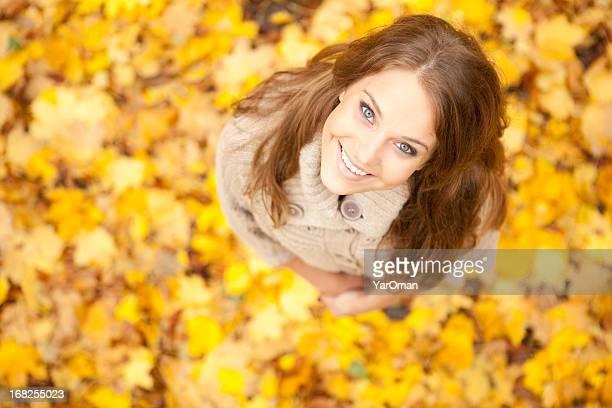 Souriante jeune femme sur fond de feuilles jaunes