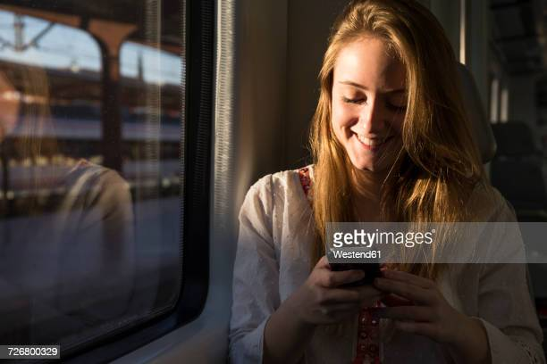Smiling young woman on a train looking at cell phone
