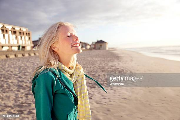 Smiling young woman on beach at sunrise with closed eyes