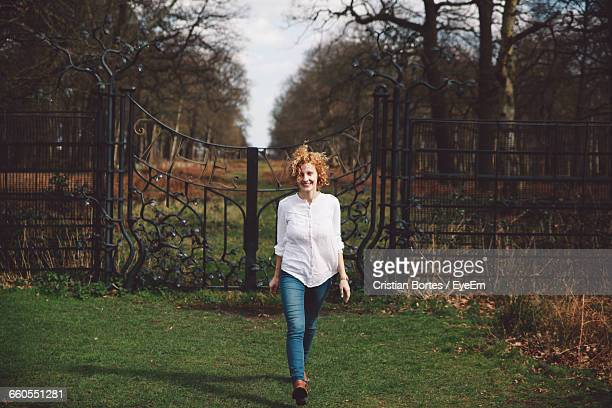 smiling young woman on grassy field walking against closed gate - bortes stockfoto's en -beelden