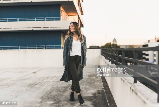 smiling young woman on parking level in the city - coat ストックフォトと画像