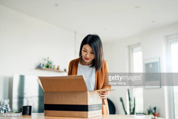 smiling young woman opening a delivery box in the living room - open stock pictures, royalty-free photos & images