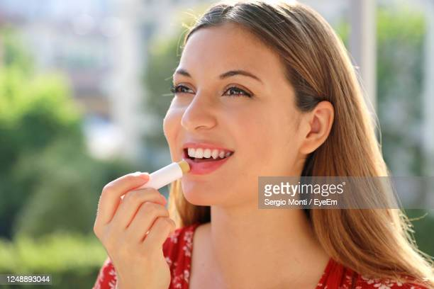 smiling young woman outdoors - lip balm stock pictures, royalty-free photos & images