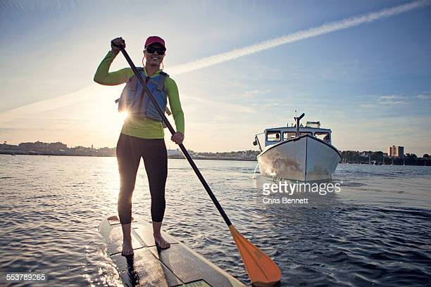 a smiling young woman paddleboards across the harbor in portland, maine at sunset. - portland maine fotografías e imágenes de stock