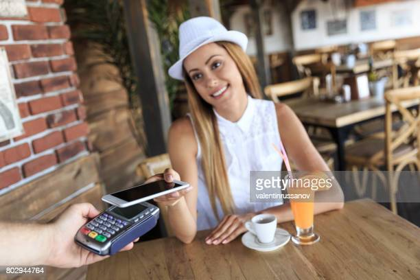 Smiling young woman paying with smart phone in cafeteria