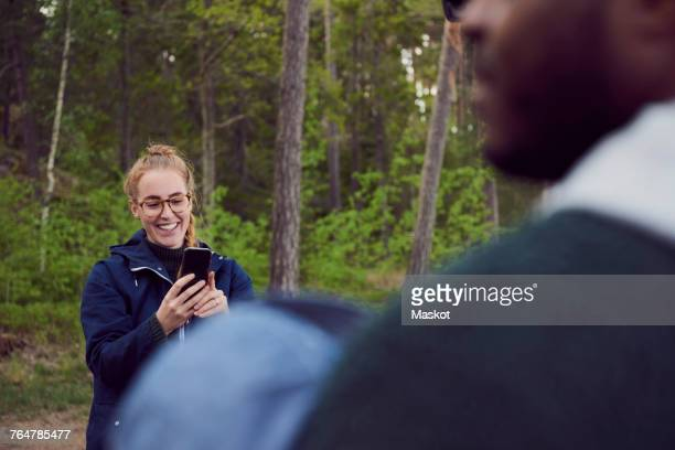 Smiling young woman photographing man with baby boy in forest