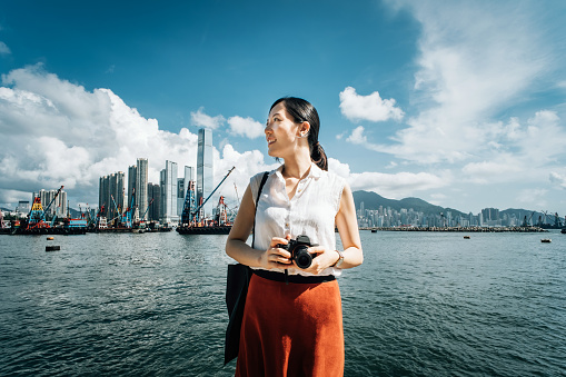 Smiling young woman photographing with camera against iconic city skyline and busy commercial dock on a sunny day - gettyimageskorea