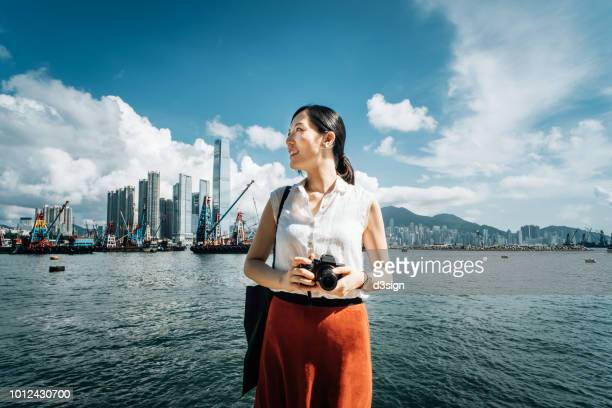 Smiling young woman photographing with camera against iconic city skyline and busy commercial dock on a sunny day