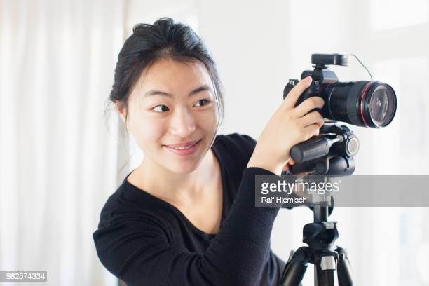 Smiling young woman photographing with camera