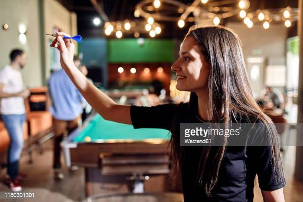 smiling young woman playing darts - darts stock pictures, royalty-free photos & images
